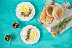 Labneh-labanehmiddle Ziegenmilchkäse östliches weiches mit Olivenöl, za 'atar, Zitrone, Pittabrot, gedient an traditionellem Konz stockbilder