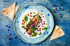 Labneh middle eastern lebanese cream cheese dip with roasted aubergine, pomegranate, mint and pita. Royalty Free Stock Photography