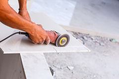 Labor cutting tile floor for new house building Stock Images