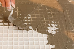 Labor cutting tile floor for new house building Stock Photo