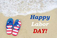 Labor day background on the beach. Labor day background on the sandy beach with flip flops of American flag colors Royalty Free Stock Images