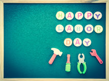 Labor day background concept. Happy labor day text with tools toy on greenboard background top view Stock Photo