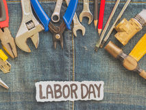 Labor day background concept. Jeans, many handy tools with labor day text on Jeans background top view Stock Photos