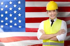Labor day concept. Smiling asian worker man in safety vest and yellow helmet standing with american flag background. Labor day concept stock photo