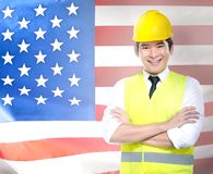 Labor day concept. Smiling asian worker man in safety vest and yellow helmet standing with american flag background. Labor day concept stock image