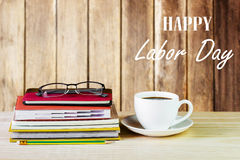 Labor Day is a federal holiday of United States America. Cup of Coffee, glasses and stack of book on wooden table with blurred wood background. Business Royalty Free Stock Photography