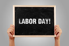 Labor Day. Hands holding small blackboard with text Labor Day against gray background Stock Photography