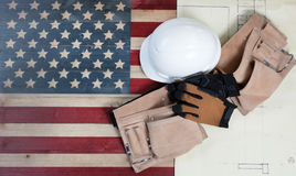 Labor Day holiday for United States of America. Labor Day background with USA rustic wooden flag, drawing blue prints and used industrial tools plus utility belt Stock Images