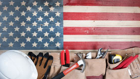Labor Day holiday for United States of America with worker tools. Labor Day background with USA rustic wooden flag and utility belt plus hard hat Stock Image