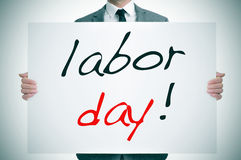 Labor day. A man wearing a suit holding a signboard with the text labor day written in it Stock Images