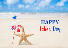 Labor Day USA background with starfishes. And decorations on the sandy beach Stock Images