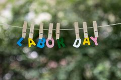 Labor Day word hanging by rope with beautiful green nature bokeh background, retro vintage tone stock images