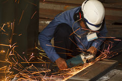 Labor with electric wheel grinding. In workshop Stock Image