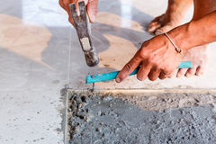 Labor installing tile floor for new house building Royalty Free Stock Photo