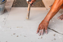 Labor installing tile floor for new house building Royalty Free Stock Images