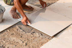 Labor installing tile floor for new house building Stock Image