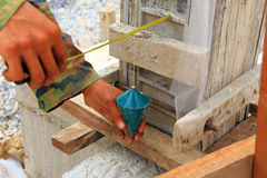 Labor man using a plumb bob for check. A labor man using a plumb bob for check Royalty Free Stock Photo