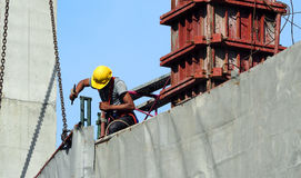 Labor man working on construction site with helmet. Labor man working on construction site with helmet and safty equipment and covering the building with grey Royalty Free Stock Photos