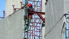 Labor man working on construction site with helmet. Labor man working on construction site with helmet and safty equipment and covering the building with grey Royalty Free Stock Photography