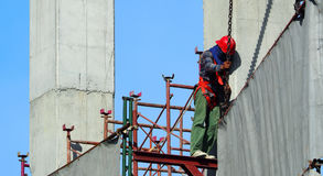 Labor man working on construction site with helmet. Labor man working on construction site with helmet and safty equipment and covering the building with grey Stock Image