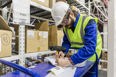 Labor wearing uniform and hard hat writing Stock Photography