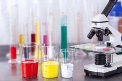 Laborancki mikroskop z farbami Zdjęcia Stock
