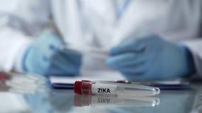 Laboranckiego asystenta writing rezultaty Zika wirusa badanie, kontrola chorób obrazy stock