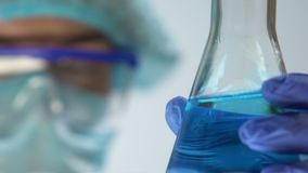 Laboranckiego pracownika mienia kolba z błękitnym cieczem, gospodarstwo domowe substancji chemicznych produkcja zbiory