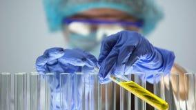 Laborant, der pH-Niveau in der gelben Flüssigkeit mit Lackmuspapier, Urinprobe misst stock footage