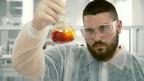 Laborant som blandar röd flytande i en flaska stock video