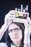 Laborant som undersöker en grupp av kemikalieer i flaskor i laboratorium Royaltyfria Bilder
