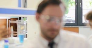 Laboratório diverso que fala, uma comunicação de Team Of Scientists Working In dos pesquisadores video estoque