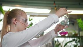 Laboratório químico Mulher loura nova que derrama o líquido de uma garrafa a outra video estoque