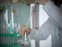 Laboratoire chimique Jeune femme tenant un flacon, s'égouttant quelque chose utilisant la pipette Le liquide change sa couleur images libres de droits