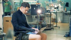 Laboratoire d'ordinateur avec un jeune homme avec une main prosthétique fonctionnant avec un ordinateur portable Concept de cybor banque de vidéos
