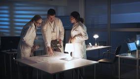 Laboratoire de recherche de technologie : Groupe divers d'ingénieurs discutant le développement de l'électronique avec la carte m banque de vidéos