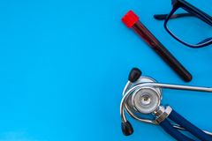 Laboratorial plastic tube with blood for analysis and stethoscope on blue background occupy half of photo, in second half - empty royalty free stock images