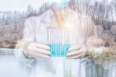 A laboratorian in mask and gloves is holding a set of test tubes with nature water samples stock photography