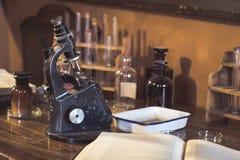 Laboratorio antiguo, microscopio y tubos de cristal Fotos de archivo