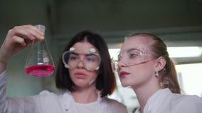 Laboratorio chimico Due assistenti medici delle giovani donne che fanno gli esperimenti stock footage