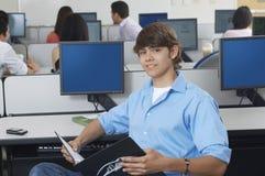 Laboratorio del computer di With Book In dello studente maschio Fotografie Stock Libere da Diritti