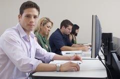 Laboratorio del ordenador de With Classmates In del estudiante masculino imagen de archivo