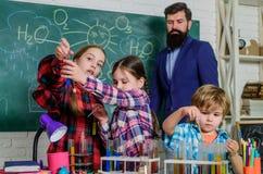 Laboratorio di chimica della scuola Di nuovo al banco Concetto educativo Allievi nella classe di chimica insegnante felice dei ba fotografie stock