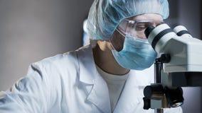 Laboratorium hulp het bekijken steekproeven in microscoop, die chemisch onderzoek leiden stock foto