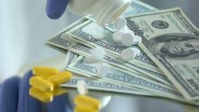 Laboratorium hulp het dalen pillen op dollars, investering in medisch onderzoek, close-up stock video
