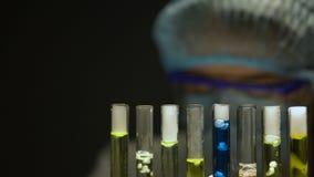 Laboratorium hulp toevoegende chemische agens in reageerbuis en het schrijven resultaten, onderzoek stock footage