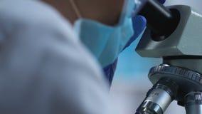 Laboratoriumarbeider die zorgvuldig steekproef onderzoeken onder microscoop, medisch onderzoek stock videobeelden