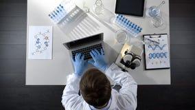 Laboratoriumarbeider het bekijken steekproeven onder microscoop en het typen resultaten op laptop topview stock afbeeldingen