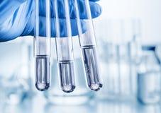 Laboratoriumdryckeskärlar i hand för analytiker` s royaltyfri foto