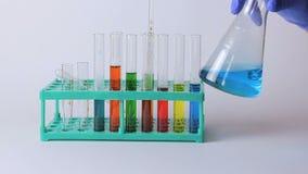 Laboratoriumflaskor och dryckeskärlar på tabellen arkivfilmer